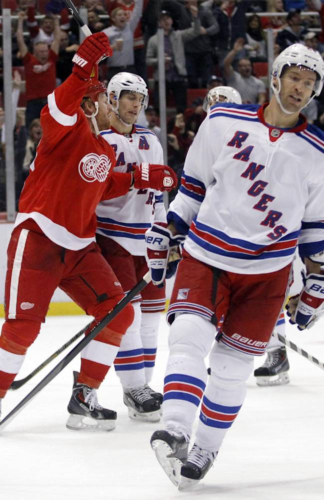 Detroit Red Wings left wing Johan Franzen, left, celebrates a second period goal by teammate Daniel Alfredsson as New York Rangers center Dominic Moore, right, skates away during an NHL hockey game Saturday, Oct. 26, 2013, in Detroit