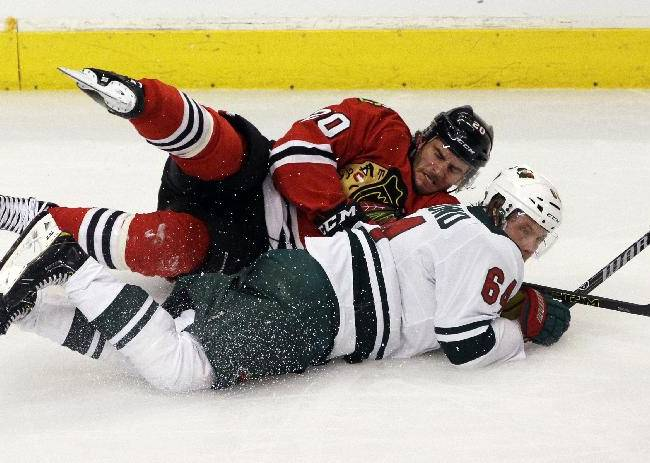 Chicago Blackhawks' Brandon Saad (20), top, is checked by Minnesota Wild's Mikael Granlund (64) during the third period in Game 2 of an NHL hockey second-round playoff series in Chicago, Sunday, May 4, 2014. The Blackhawks won 4-1