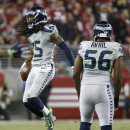 Seattle Seahawks cornerback Richard Sherman (25) celebrates next to defensive end Cliff Avril (56) after intercepting San Francisco 49ers quarterback Colin Kaepernick during the fourth quarter of an NFL football game in Santa Clara, Calif., Thursday, Nov. 27, 2014. (AP Photo/Tony Avelar)