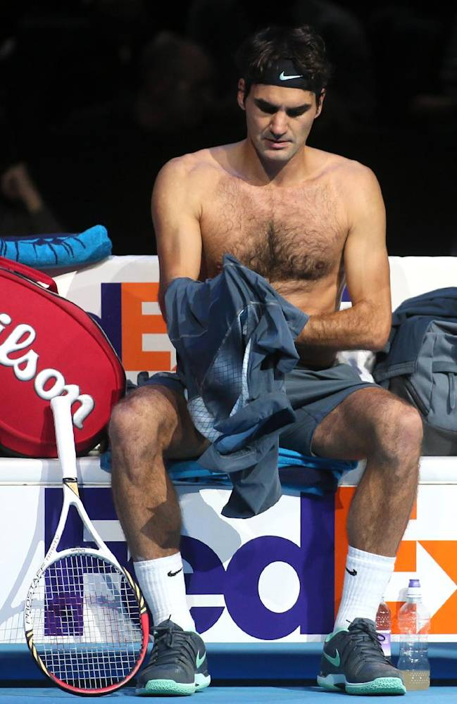 Roger Federer of Switzerland changes his shirt during a break in his match against Juan Martin Del Potro of Argentina during their ATP World Tour Finals tennis match at the O2 Arena in London, Saturday, Nov. 9, 2013