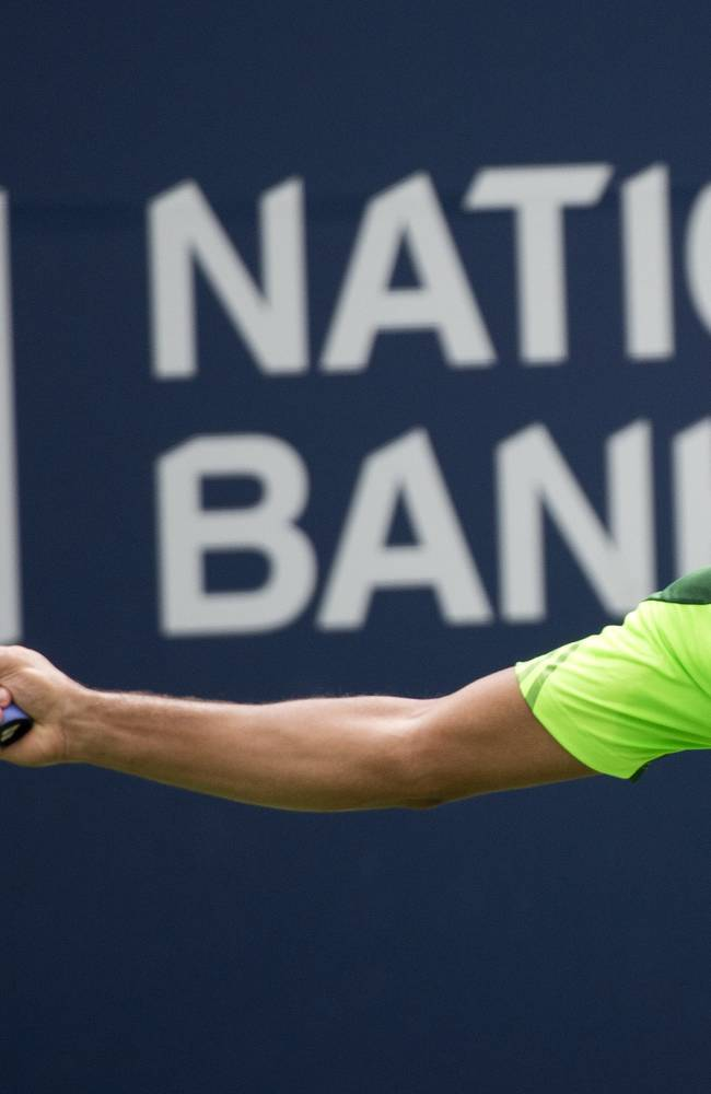Jo-Wilfried Tsonga, of France, returns the ball against Novak Djokovic, of Serbia, in a men's third round match at the Rogers Cup tennis tournament action in Toronto Thursday, Aug. 7, 2014