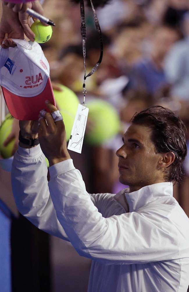 Rafael Nadal of Spain signs autographs following his first round win over Bernard Tomic of Australia at the Australian Open tennis championship in Melbourne, Australia, Tuesday, Jan. 14, 2014