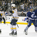 Buffalo Sabres' Tyler Ennis, left, celebrates scoring his team's second goal as Sabres' Zemgus Girgensons, second from left, Toronto Maple Leafs' Jay McClement and Nikolai Kulemin, right, looks on during the third period in an NHL hockey game, Saturday,