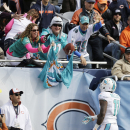 Miami Dolphins wide receiver Mike Wallace (11) throws a ball to fans after scoring a touchdown during the first half of an NFL football game against the Chicago Bears Sunday, Oct. 19, 2014 in Chicago The Associated Press