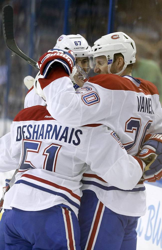 Montreal Canadiens left wing Thomas Vanek (20), of Austria, celebrates with teammates Max Pacioretty (67) and David Desharnais (51) after scoring against the Tampa Bay Lightning during the third period of Game 1 of a first-round NHL hockey playoff series on Wednesday, April 16, 2014, in Tampa, Fla