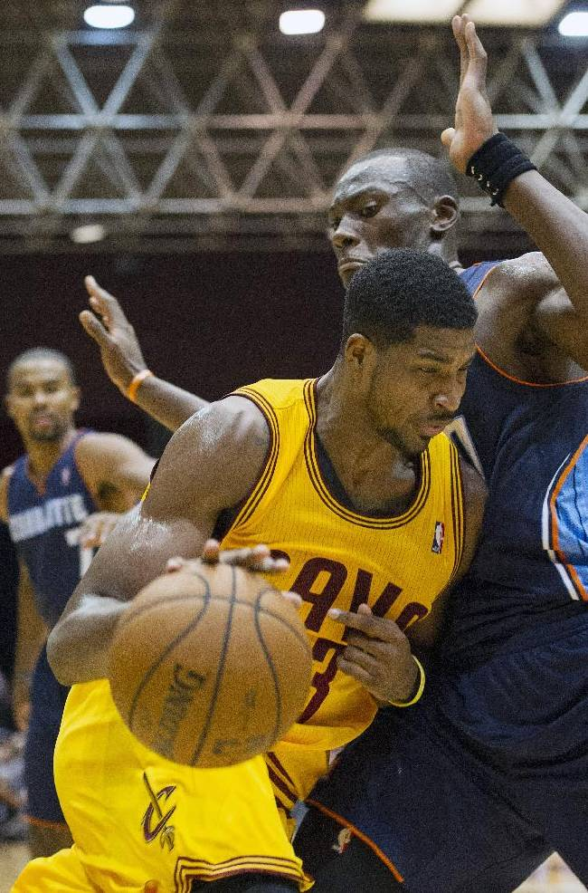 Cleveland Cavaliers forward Tristan Thompson, left, drives into Charlotte Bobcats defender Bismark Biyombo during the first quarter of an NBA preseason basketball game in Canton, Ohio, Tuesday, Oct. 15, 2013