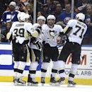 Pittsburgh Penguins left wing David Perron (39), defenseman Paul Martin (7), Sidney Crosby (87), defenseman Kris Letang (58) and center Evgeni Malkin (71) celebrate Crosby's goal in the second period of an NHL hockey game against the New York Islanders a