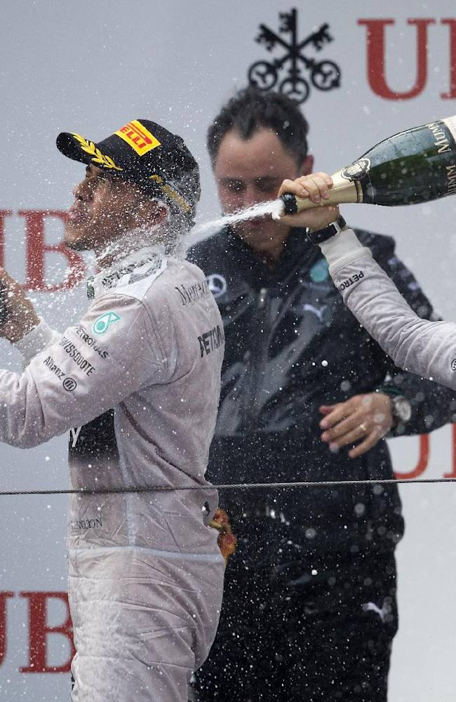 Mercedes driver Lewis Hamilton of Britain, left, is sprayed champaign by his teammate Nico Rosberg of Germany after the Chinese Formula One Grand Prix at Shanghai International Circuit in Shanghai, China Sunday, April 20, 2014