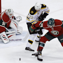 Minnesota Wild defenseman Nate Prosser (39) and Boston Bruins right wing Shawn Thornton (22) chase the puck as Wild goalie Ilya Bryzgalov (30), of Russia, covers the net during the first period of an NHL hockey game in St. Paul, Minn., Tuesday, April 8, 2