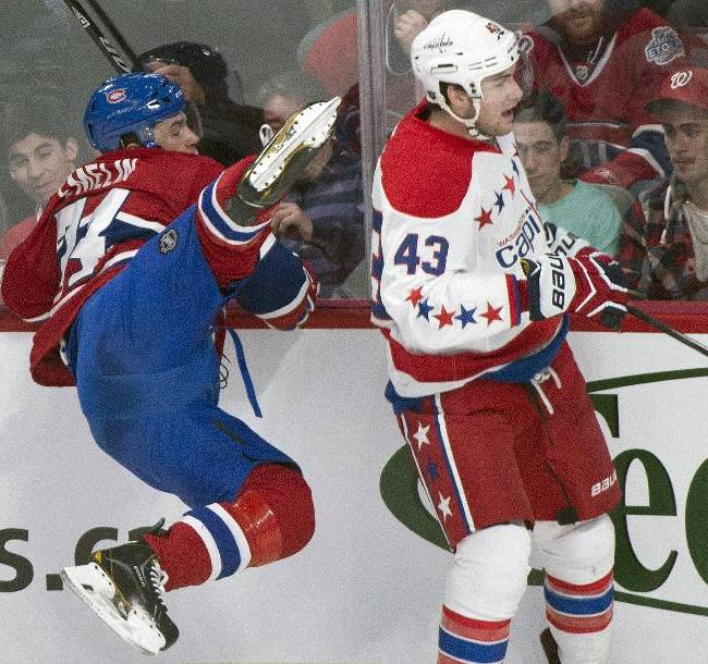 Montreal Canadiens' Alexei Emelin, left, is upended by Washington Capitals' Tom Wilson during the first period of an NHL hockey game in Montreal, Saturday, Jan. 25, 2014