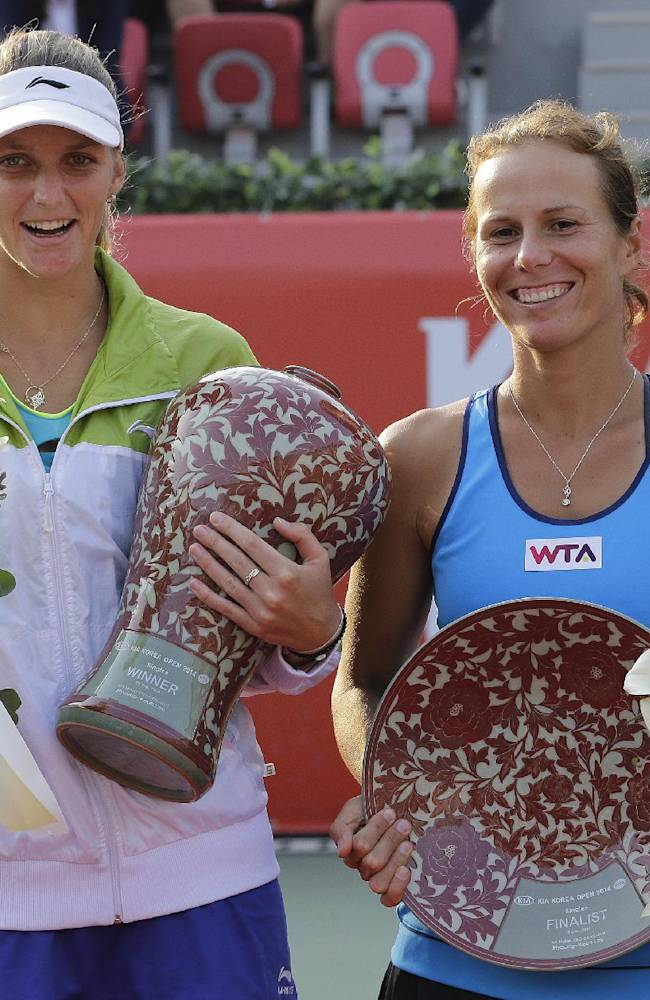 Karolina Pliskova, left, of Czech Republic holds the winner's trophy as Varvara Lepchenko of the United States holds the second placed trophy at the final match of the Korea Open tennis in Seoul, South Korea, Sunday, Sept. 21, 2014. Pliskova won the match 6-3, 6-7, 6-2