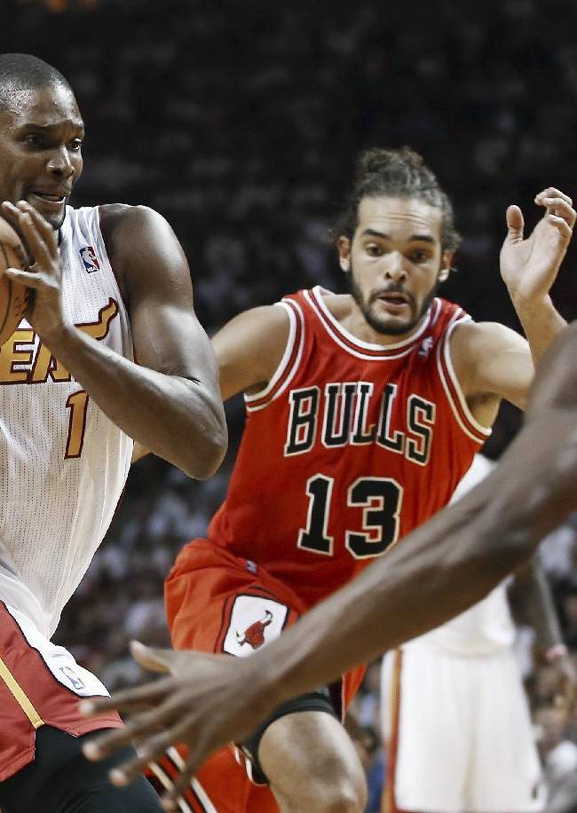 Miami Heat's Chris Bosh (1) tries to drive between Chicago Bulls' Joakim Noah (13) and Jimmy Butler (22) during the first half of an NBA basketball game in Miami, Tuesday, Oct. 29, 2013