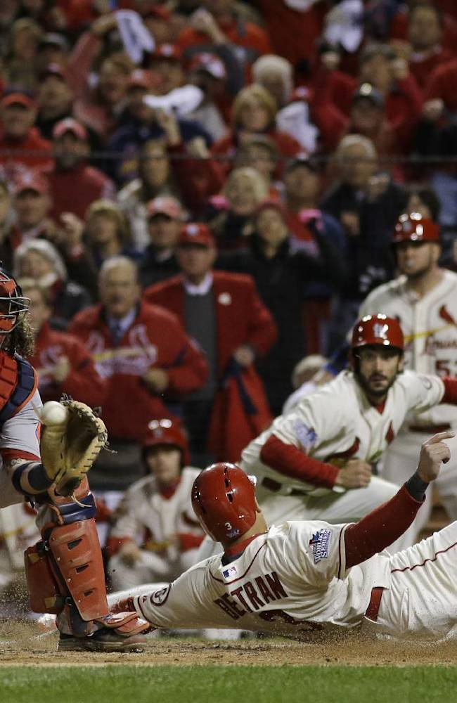 St. Louis Cardinals' Carlos Beltran slides safely past Boston Red Sox catcher Jarrod Saltalamacchia during the seventh inning of Game 3 of baseball's World Series Saturday, Oct. 26, 2013, in St. Louis. Beltran scored from second on a double by Matt Holliday