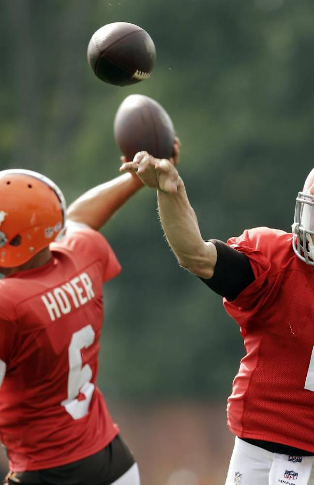 In this Aug. 12, 2014, file photo, Cleveland Browns quarterbacks Johnny Manziel (2) and Brian Hoyer throw a pass during NFL football practice at the team's training camp in Berea, Ohio. heir helmet-to-helmet, throw-for-throw competition down to its final days