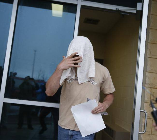 Former Minnesota quarterback Philip Nelson leaves the Blue Earth Co jail with a towel on his head after posting $20,00 bail in his assault case stemming from a fight outside a bar that left another former football player in critical condition with head injuries, in Mankato, Minn, Monday, May 12, 2014. Authorities say Nelson kicked Isaac Dallas Kolstad, 24, in the head after another man punched and knocked him to the ground early Sunday as bars were closing in Mankato
