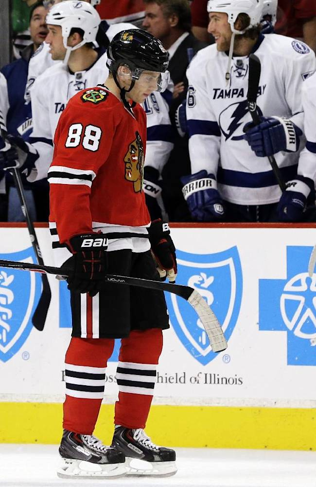 Chicago Blackhawks' Patrick Kane skates to bench after missing a shot against the Tampa Bay Lightning during the shootout of an NHL hockey game in Chicago, Saturday, Oct. 5, 2013. The Lightning won 3-2