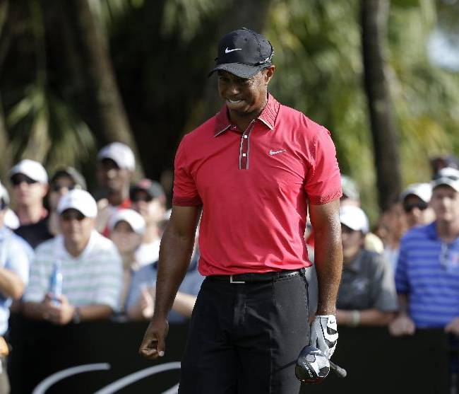 Tiger Woods grimaces after teeing off on the 12th hole during the final round of the Cadillac Championship golf tournament Sunday, March 9, 2014, in Doral, Fla. Woods' back was flaring up after hitting out of a bunker on the sixth hole