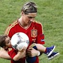 Spain's Fernando Torres leaves the pitch with his son Leo after defeating Italy to win the Euro 2012 final soccer match at the Olympic stadium in Kiev, July 1, 2012. REUTERS/Michael Dalder