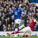 Everton's Romelu Lukaku, centre, fights for the ball against Arsenal's Thomas Vermaelen during their English Premier League soccer match at Goodison Park Stadium, Liverpool, England, Sunday April 6, 2014