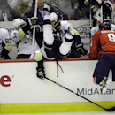 Pittsburgh Penguins center Brandon Sutter, center, goes over the wall into the bench after he was hit by Washington Capitals right wing Alex Ovechkin (8), of Russia, during the third period of an NHL hockey game, Monday, March 10, 2014, in Washington. Als