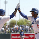Los Angeles Dodgers' Hanley Ramirez (13) is congratulated by Carl Crawford after hitting a two-run home run against the Texas Rangers during an exhibition baseball game in Glendale, Ariz., Friday, March 7, 2014 The Associated Press