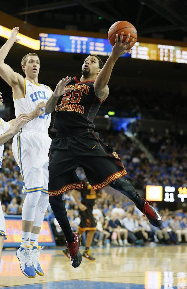 Southern California's J.T. Terrell, right, goes to the basket in front of UCLA's Travis Wear, left, during the first half of an NCAA college basketball game on Sunday, Jan. 5, 2014, in Los Angeles