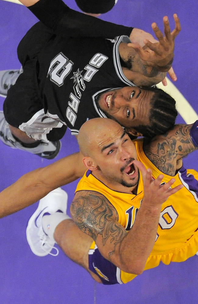 Los Angeles Lakers center Robert Sacre, below, and San Antonio Spurs forward Kawhi Leonard battle for a rebound during the second half of their NBA basketball game, Wednesday, March 19, 2014, in Los Angeles. The Spurs won 125-109