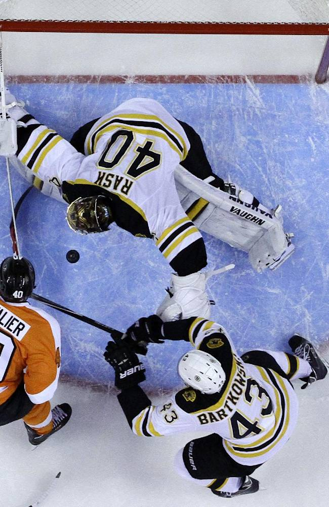 Philadelphia Flyers' Vincent Lecavalier, left, tries to shoot past Boston Bruins' Tuukka Rask, top, of Finland, and Matt Bartkowski (43) during the second period of an NHL hockey game on Sunday, March 30, 2014, in Philadelphia