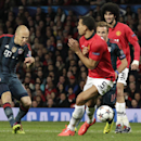 Bayern's Arjen Robben, left, shoots past Manchester United's Rio Ferdinand during the Champions League quarterfinal first leg soccer match between Manchester United and Bayern Munich at Old Trafford Stadium, Manchester, England, Tuesday, April 1, 2014
