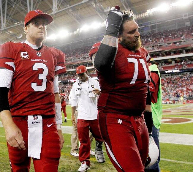 Arizona Cardinals' Carson Palmer (3) and Daryn Colledge (71) walk off the field after an NFL football game loss to the San Francisco 49ers Sunday, Dec. 29, 2013, in Glendale, Ariz.  The 49ers won 23-20