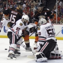 Chicago Blackhawks defenseman Johnny Oduya (27), of Sweden, and goalie Corey Crawford (50) defend against a flying puck, next to Anaheim Ducks center Ryan Getzlaf (15) and right wing Corey Perry during the second period of an NHL hockey game in Anaheim,