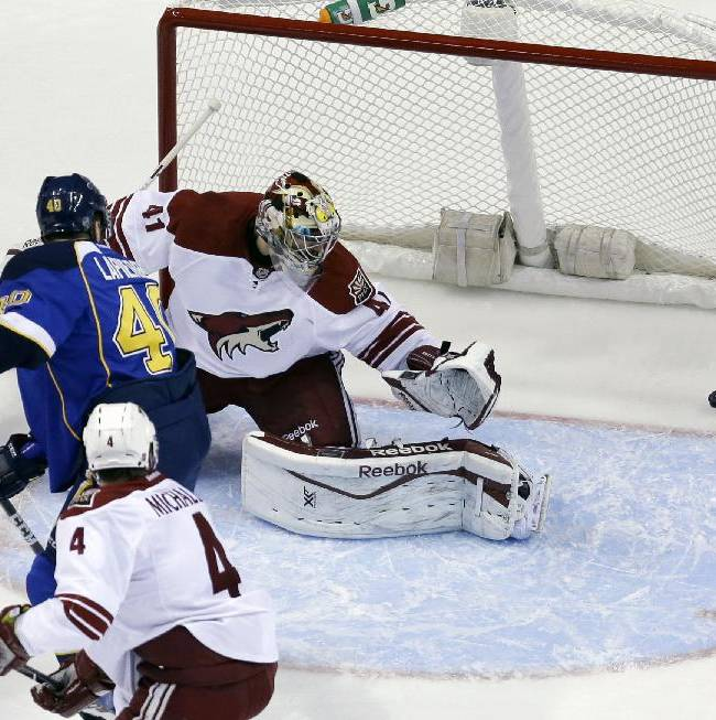 St. Louis Blues' Maxim Lapierre, center, scores on a deflection past Phoenix Coyotes goalie Mike Smith (41) as Coyotes' Zbynek Michalek (4), of Czech Republic, stands by during the first period of an NHL hockey game Tuesday, Nov. 12, 2013, in St. Louis