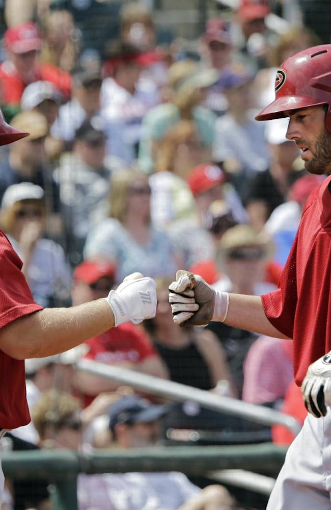 Arizona Diamondbacks' Nick Evans, right, is greeted by teammate Garrett Weber (15) after hitting a solo home run off Cincinnati Reds starting pitcher Tony Cingrani in the fourth inning of a spring exhibition baseball game on Thursday, March 27, 2014, in Goodyear, Ariz