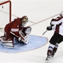 Colorado Avalanche's P.A. Parenteau, right, scores the game-winning goal against Phoenix Coyotes' Mike Smith during the shoot