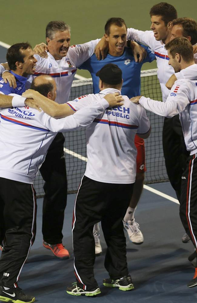Lukas Rosol, center top, Radek Stepanek, left and other team members of the Czech Republic celebrate after defeating Japan during quarterfinal of Davis Cup World Group tennis at Ariake Colosseum in Tokyo, Saturday, April 5, 2014