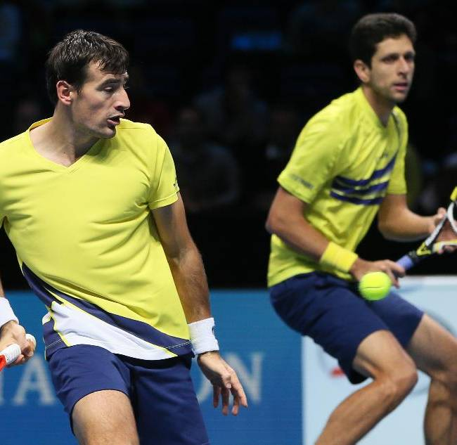Ivan Dodig of Croatia, left, watched by partner Marcelo Melo of Brazil, plays a return to David Marrero of Spain and Fernando Verdasco of Spain during their ATP world Tour Finals semi-final tennis match at the O2 Arena on London, Sunday, Nov. 10, 2013