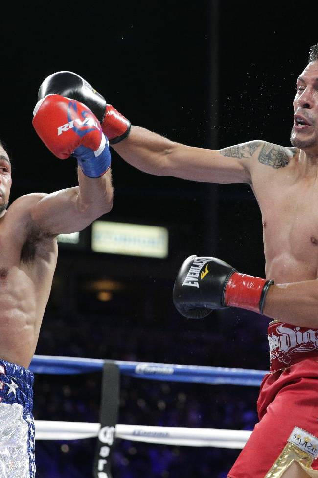 Keith Thurman, left, and Julio Diaz trade punches during the second round of a WBA interim welterweight title boxing match on Saturday, April 26, 2014, in Carson, Calif. Thurman won by TKO after the third round. Diaz wasn't able to come out for the fourth round due to his rib injury