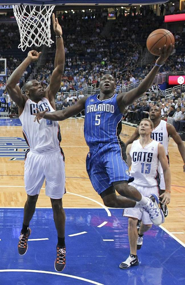 Orlando Magic's Victor Oladipo (5) drives to the basket for a shot past Charlotte Bobcats' Bismack Biyombo, left, Luke Ridnour (13) and Anthony Tolliver, right, during the first half of an NBA basketball game in Orlando, Fla., Friday, March 28, 2014