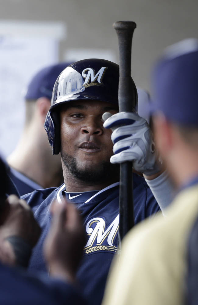Milwaukee Brewers' Juan Francisco is greeted in the dugout after hitting his second home run against the Oakland Athletics during the fourth inning of a spring training baseball game on Thursday, Feb. 27, 2014, in Scottsdale, Ariz