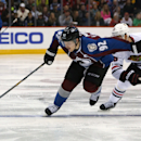 Colorado Avalanche left wing Gabriel Landeskog, left, of Sweden, reaches for puck as Chicago Blackhawks center Jonathan Toews defends during the third period of the Blackhawks' 3-2 victory in an NHL hockey game in Denver on Wednesday, Nov. 26, 2014 The As