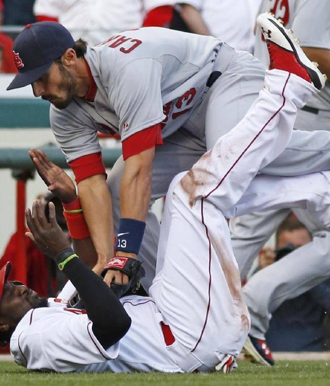 St. Louis Cardinals third baseman Matt Carpenter, top, tags out Cincinnati Reds' Brandon Phillips after Phillips was caught in a rundown between third base and home in the eighth inning of a baseball game, Monday, March 31, 2014, on opening day in Cincinnati. St. Louis won 1-0