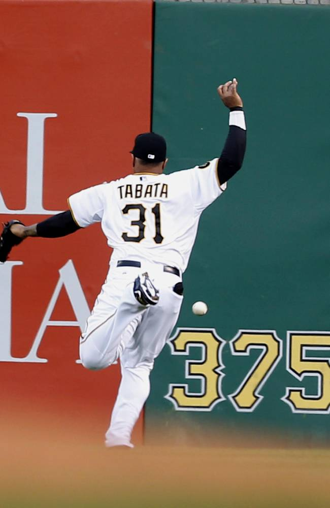 Pittsburgh Pirates right fielder Jose Tabata can't get to a fly ball hit by Milwaukee Brewers' Jonathan Lucroy in the second inning of a baseball game Saturday, April 19, 2014, in Pittsburgh. Lucroy later came in to score on a hit by Khris Davis