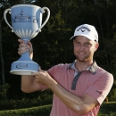Chris Kirk holds up the trophy after winning the Deutsche Bank Championship golf tournament in Norton, Mass., Monday, Sept. 1, 2014. (AP Photo/Michael Dwyer)