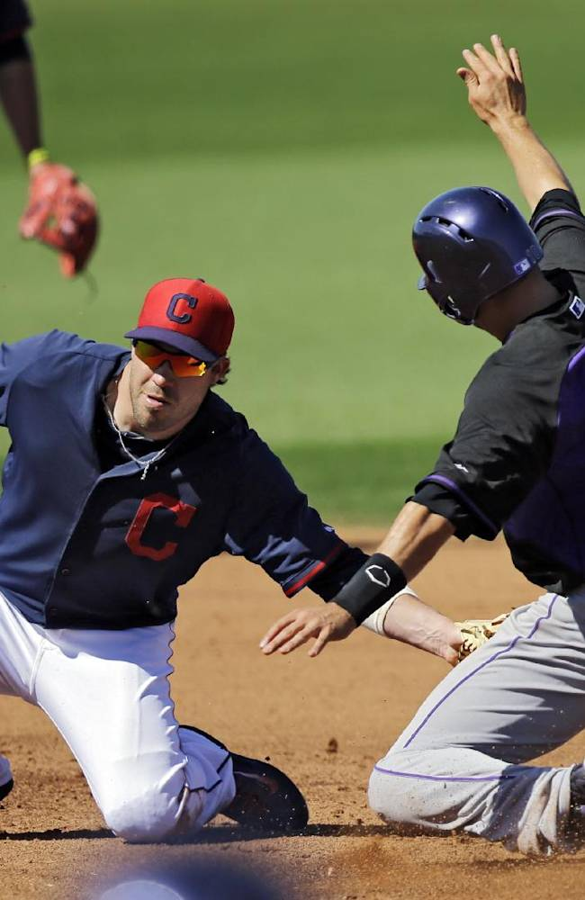 Cleveland Indians second baseman Jason Kipnis tags out Colorado Rockies' Paul Janish (10) attempting to steal second base in the fifth inning of a spring exhibition baseball game, Saturday, March 22, 2014, in Goodyear, Ariz