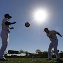 Los Angeles Dodgers' Brendan Harris, left, and A.J. Ellis workout with a heavy ball during spring training baseball practice Thursday, Feb. 20, 2014, in Glendale, Ariz The Associated Press