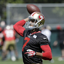 In this June 17, 2014 file photo, San Francisco 49ers quarterback Colin Kaepernick (7) passes during an NFL football minicamp in Santa Clara, Calif. Kaepernick is rich with a new contract that got done before training camp, as everybody hoped. He's ready