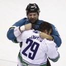 San Jose Sharks' John Scott, top, fights with Vancouver Canucks' Tom Sestito during the first period of an NHL preseason hockey game Tuesday, Sept. 23, 2014, in Stockton, Calif. The Associated Press