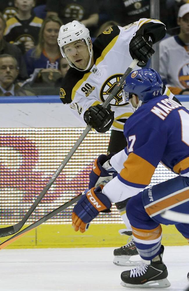 Boston Bruins' Jarome Iginla, left, takes a shot past New York Islanders' Andrew MacDonald during the first period of the NHL hockey game, Monday, Jan. 27, 2014, in Uniondale, New York
