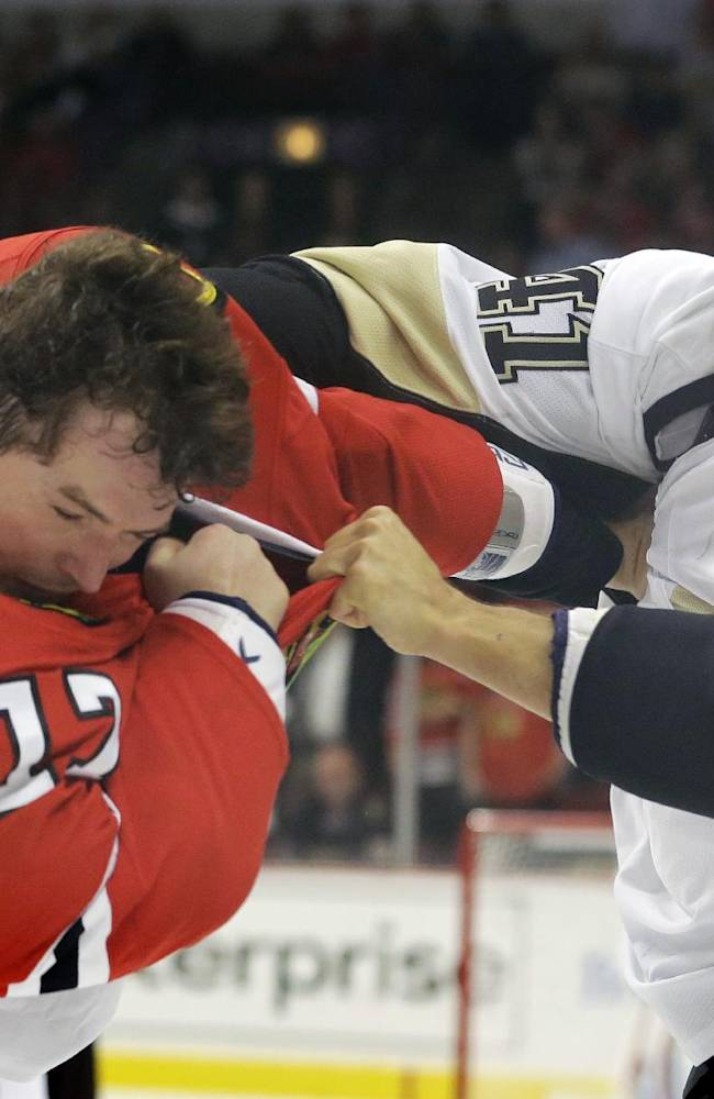 Pittsburgh Penguins' Robert Bortuzzo, right, fights with Chicago Blackhawks' Sheldon Brookbank during the first period of an NHL preseason hockey game in Chicago, Thursday, Sept. 19, 2013