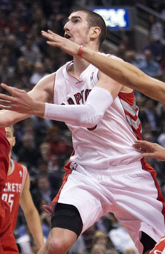 Toronto Raptors guard Nando De Colo, center, drives up the middle past Houston Rockets' Omer Asik, left, and Jeremy Lin, right, during first-half NBA basketball action in Toronto, Wednesday, April 2, 2014
